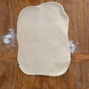 a portion of bread dough rolled out on wooden board