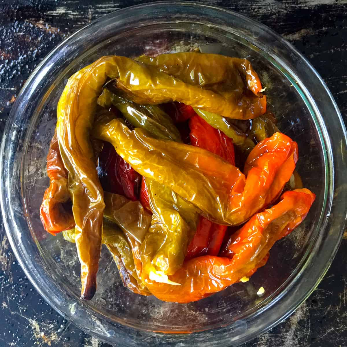 glass bowl with red and green Italian long hot peppers on baking sheet