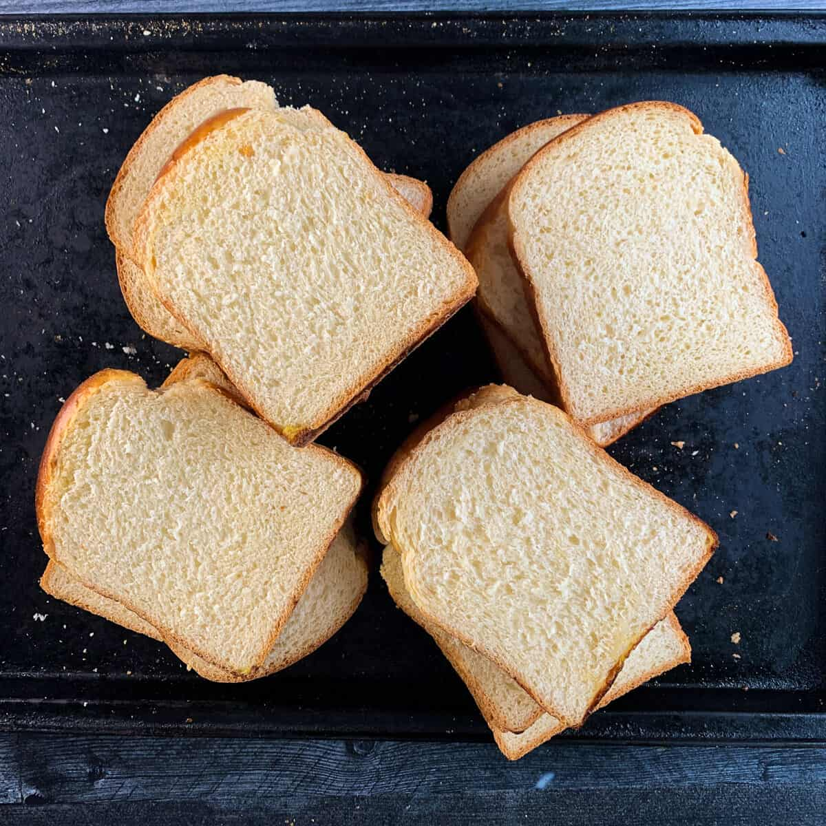 slices of shokupan (sandwich bread) on black baking tray