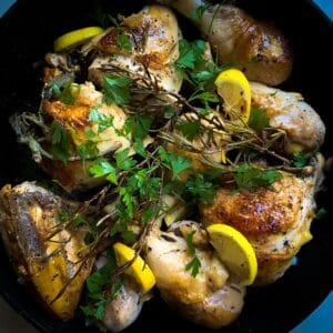 top view of cooked Mediterranean (Italian) skillet roasted chicken with fresh herbs and lemon