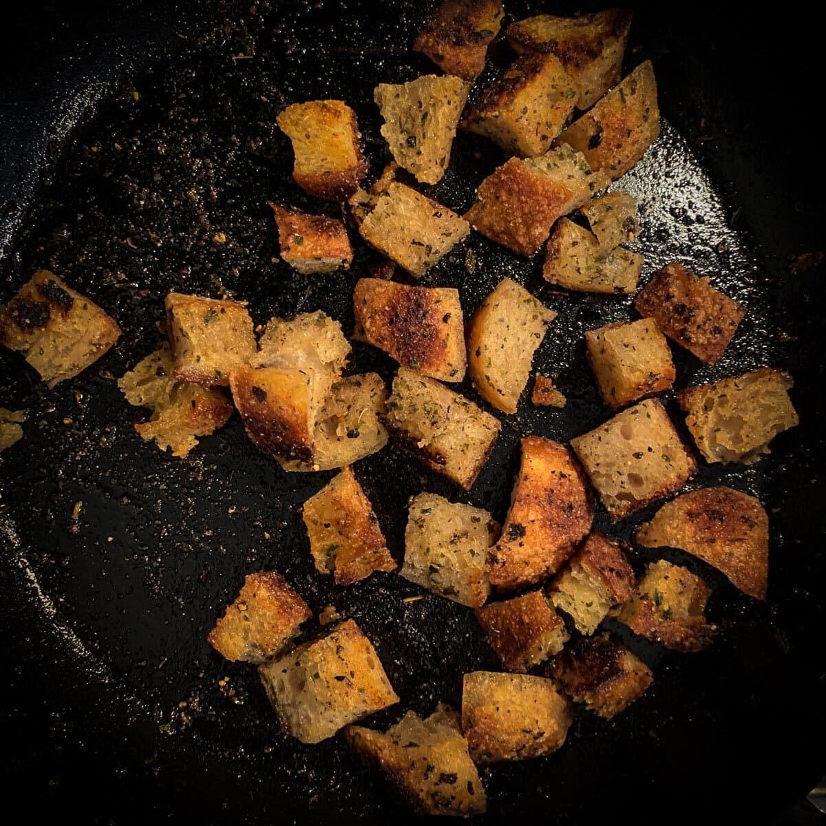 top view of seasoned croutons in black pan
