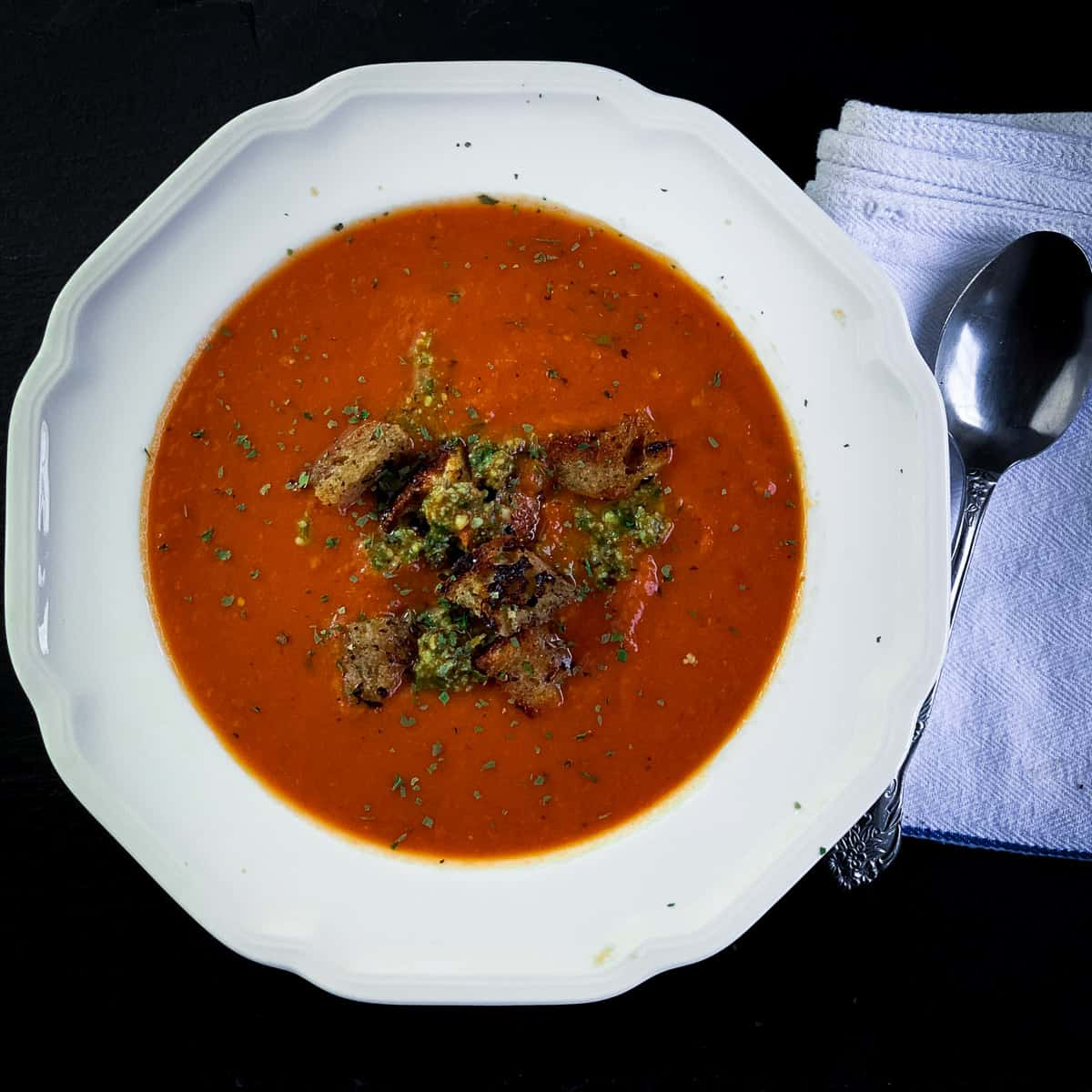 Top view of tomato soup in white bowl with spoon and white napkin