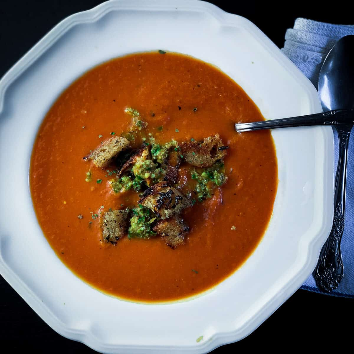tomato soup with spoon in white bowl