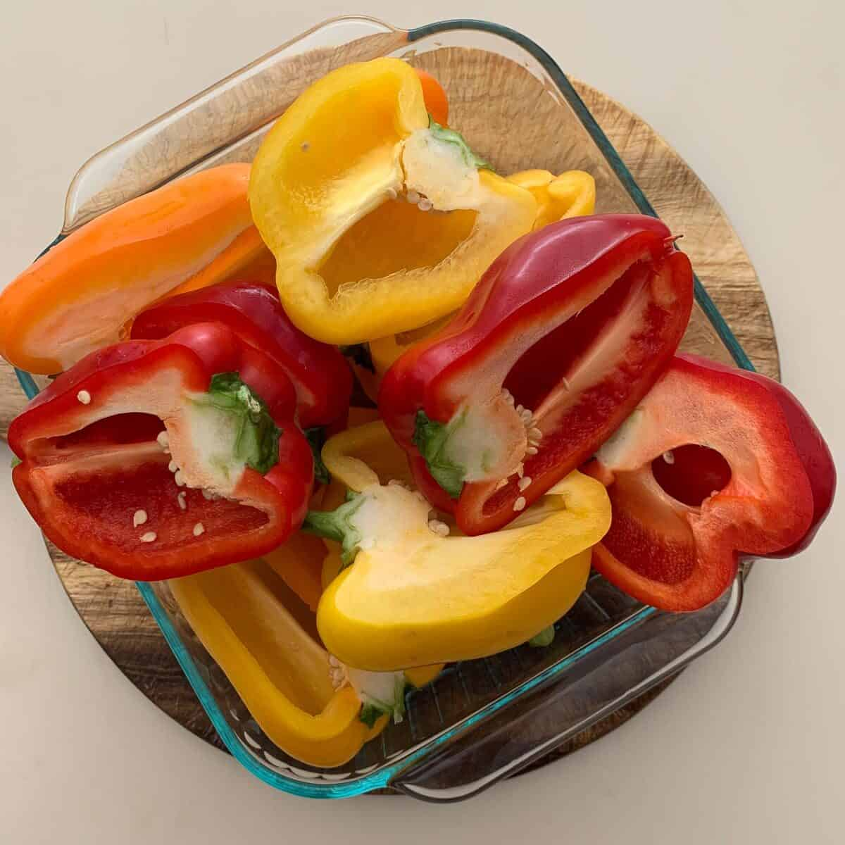 raw bell peppers cut in half in square glass dish
