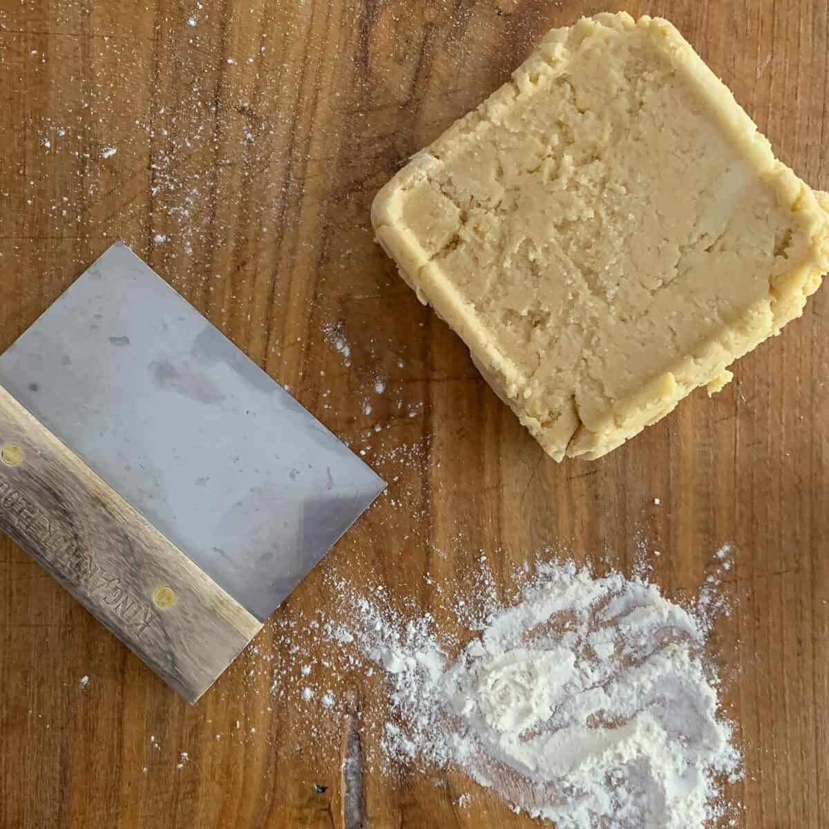 cookie dough after refrigerating on wooden board with flour and bench knife